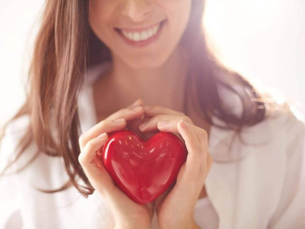 woman holding out red heart